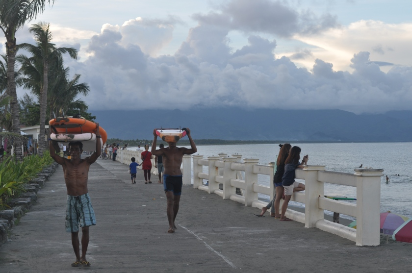 AFTER ANOTHER DAY, local surfers go home carrying surf boards on their head.